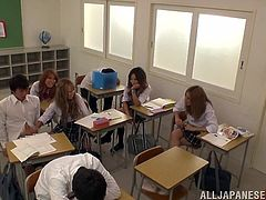 Sexy Japanese babe in school uniform takes a dick out of guys pants right in a classroom. She makes him cum while other girls watch at this.