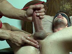 Blindfolded and tied up brunette dude gets tied up by the man. After that he gets an amazing handjob.