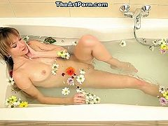 Soaked in hot water and colored flowers, Angel Piaff is using the water jet to tease her pink pussy.