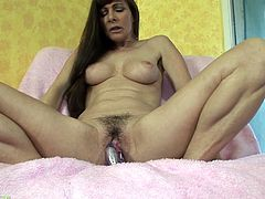 Hit play and enjoy the visuals of this brunette milf sticking a hard toy in her hairy pierced pussy as she masturbates for the camera.