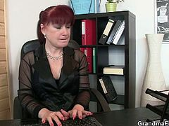 This redhead granny sits at her desk when two men come in her office. She decides to play with their cocks.