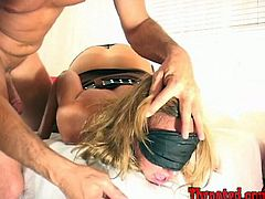 Stunning blonde girl in stockings with a sleep mask on her eyes stands on her knees and gets face fucked.