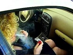 While smoking in the car, blonde milf gets horny to masturbate her twat