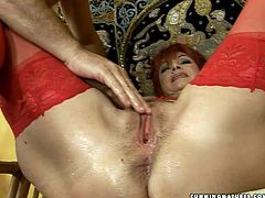 Whorish red-haired mature in raunchy red lingerie and stockings gets lured by horny bald daddy. He mauls her baggy tits from behind before she spread her legs wide to welcome a finger fuck of her wet hairy pussy.