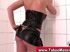 See a busty and wild redhead domme wearing a leather corset and thong while posing very sensually.