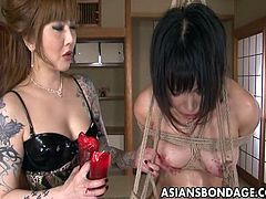 This Asian girl is tied up in rope and then brutally beaten with a piece of bamboo. Her mistress pours hot candle wax on her body. Her ass and tits are covered in hardened wax and she is in much pain but the punishment continues. Her ass is spanked harder and harder.