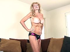 A blonde mature slut with big-ass fucking tits gets naked for the camera and starts shoving a hard toy up her fucking pussy, check it out!