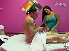 Sex greedy white tattooed dude is having a session of erotic massage. He lies on the lounge while getting his sturdy cock rubbed by a submissive Asian hottie before she welcomes his pecker inside her mouth.
