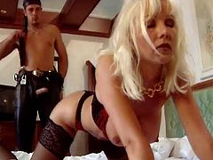 Lustful blonde woman in stockings and lingerie gives a blowjob to some cocky dude. After that she gets fucked deep cowgirl and from behind.