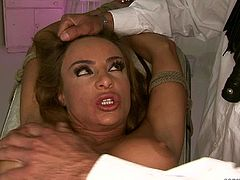 Busty light haired nympho gets fixed with ropes on the medical chair. Her legs are stretched wide and her wet pussy is opened. But horny doctor pins her nipples with some BDSM stuff and enjoys the way busty hottie moan.