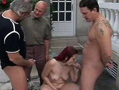 Dirty slut with long red color hair and small tits is going wild in gangbang session. Three old men are pissing onto her outdoor. She is piss drinking with pleasure.