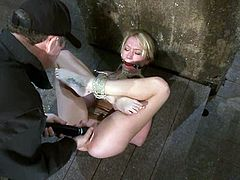 Stunning blonde chick lies on the floor being hog tied. Some guy toys her tight pink pussy and twists her tits with ropes.