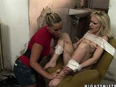Bosomy blond doxy sits on the chair with legs pulled up with her body bandaged with scotch tape while a creative domina attaches clothing pegs to her legs in BDSM-styled sex video by 21 Sextury.