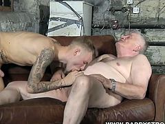 This young tattooed hunk is sucking an old man's cock after his was sucked too. They kiss each other too.