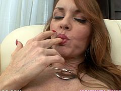 Busty Janet Mason lies on an armchair and plays with her pussy. After that she sucks the guy off and also gives him a titjob.
