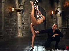 This dude ties her legs together and suspends her up high. Then he sets up and immersion tank full of water and dips this slave in it.