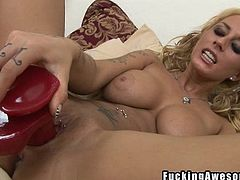 Watch this dirty slut take out one of the biggest dildos you have ever seen. It's bright red like a throbbing member. She gives it a lick and a suck and then inserts the dildo into her freshly shaved cunt. What a dirty slut she is. Watch her masturbate like a whore.