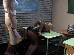 Perverse brunette professor asks to stay in class a salty blond student after studying is over. She takes off her clothes to remain in nothing but black lingerie before she is forced to bend over a table to show her ass.