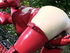Kinky woman with ample booty and big boobs is wearing latex costume and mask. She is looking hell arousing and mysterious. Secretive woman wanks with sex toy sitting on a big powerful bike.
