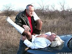 Aroused grey-haired dad takes his mature mistress to the country where they make out on a car hood. She lies on her back with legs wide open covered with lacy black stockings while he poke her missionary style.