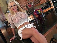 Oh fuck, I was ready to cum once I saw this utterly sexy blond doll with large enhanced tits covered with fishnet tank. She sits on the kitchen counter stroking her soaking bald pussy with manicured fingers in peppering solo sex video by Pornstar.