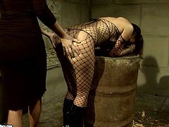 Pitiless brunette domina forces a cuddly brunette MILF in fishnet bodystocking bend down over a chair to be able to maul her juicy ass in peppering BDSM-styled sex video by 21 Sextury.