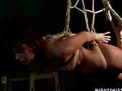 Saucy red haired slut with filthy mind has got tied up and hanged down the ceiling by her tough mistress. Then her mouth is stuffed with big sex toy so she sucks it like real juicy cock.