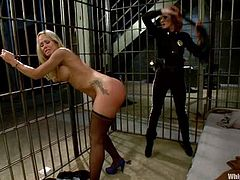 Elle Alexandra and Simone Sonay are having BDSM fun in a jail. The redhead beats the blonde's butt with a lash and then pounds her pussy with a dildo.