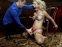 Tied and knelt the superb blonde milf gets whipped hard. All that whipping turned her on so the guy uses a vibrator to rub her clit over her red panties. That was enough to make her crave for his dick, so the executor removes her ball gag and mouth fucks her. She sucks it with pleasure and earns a big load of jizz