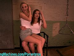 These two hot babes get fucked by two fucking machines simultaneously. The brunette helps the blonde cum.