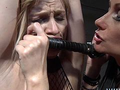 Spoiled blond whore gets suspended wearing nothing but fishnet bodystocking before a cruel red-haired domina pins her hard nipples with megal pegs in BDSM-involved sex video by 21 Sextury.
