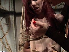 Worn out red-haired whore gets her slender body squeezed tight as she gets bandaged by rapacious domina before the later starts pinching her tits and tongue with clothing pegs in peppering BDSM sex video by 21 Sextury.