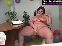 Kinky brunette wench is wearing red lingerie set. She is sitting at the table with a Bday cake in front of her. She knows she is too fat to eat that fat cake so she rubs her boobs and pussy with dessert.