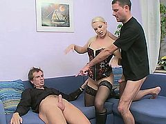 Gina Blonde sits on her couch between two guys, while wearing her thigh high stockings, along with a corset. You'll notice that she's giving these two guys a handjob and blowjob, making this a hardcore, MMF threesome, where she gets her pussy fucked while giving a blowjob, before she has her asshole reamed while giving the other man a blowjob.