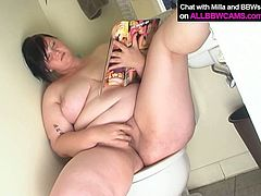 Slutty bitch with insane sex lust is sitting on a toilet tub looking at explicit XXX pictures. She get horny as fuck so she starts rubbing her pussy intensively.