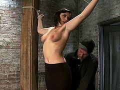 Brunette girl gets tied up between two wooden posts. After that the guy fixes claws to her tits and toys her vagina with a vibrator.