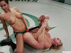 The brunette and the blonde fight in a ring. The blonde chick loses a battle, so she gets her vagina toyed with a vibrator and a strap-on.