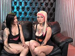 This sexy pair of tattooed bitches gets kinky with each other, as they get photographed. Watch them get nasty. The blonde licks the dark haired girl's tits and then, puts on a big strap on, and gets to pounding cunt.