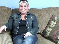 Chubby blonde mom with saggy natural tits is sitting naked on a couch. She slips her hands down caressing her slick pussy.