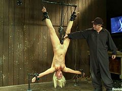 Blonde girl with perfect body gets hanged up upside down and chained. After that her master toys her pussy with a vibrator and the fucking machine.