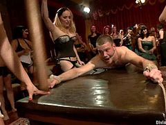 Bobbi Starr, Kimberly Kane and other girls are playing BDSM games with some dude indoors. They bind the man and play with his dick and then smash his butt with a strapon.