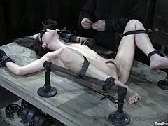 Slim babe lies on a bondage table being tied up. She gets her body clothespinned and then toyed deep in her hairy pussy.