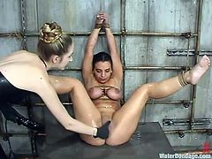 Lewd brunette Jenya is having fun with a mistress in a basement. She gets tied up and tortured and then enjoys having a massive dildo in her cunt.