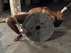 Ebony bitch Jada Fire is having BDSM fun with some guy in a basement. She lets the dude tie her up and rub her cunt with a toy and then moans loudly while being beaten with a stick.