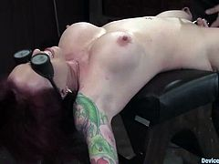 Hot redhead girl lies on a bondage table being restricted. Then the guy comes up to her and toys her pussy with a vibrator.