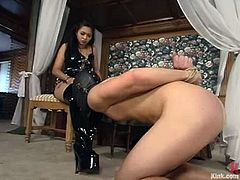 Sexy Asian girl in high boots and latex tortures guy's dick and then ties him up. After that she drills his ass with a strap-on.