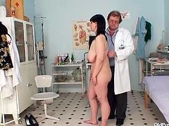 Brunette woman strips the clothes off and lies down on a bed. Then the doctor starts to shove some medical devices in old pussy.