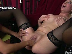 This naughty brunette in sexy black stockings is so horny that it is really scary! She pushes her fist deep inside her girlfriend's pussy and she gasps.