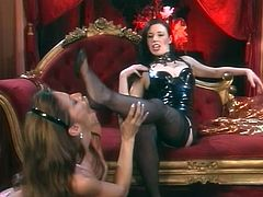 Devon Michaels the hot mistress in leather dress and stockings. She gets her feet licked by submissive Anastasia Pierce. Then Anastasia also gets her feet whipped.