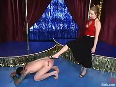 Daemon and Princess Kali are having fun in a club. The dominatrix whips Daemon with a lash and then makes him lick her feet and fucks his ass with a strapon doggy style.